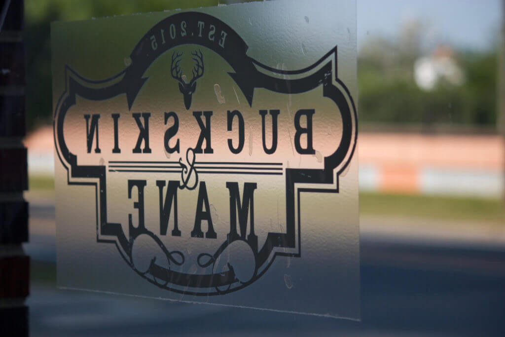 Photo of Buckskin & Mane office window having its logo