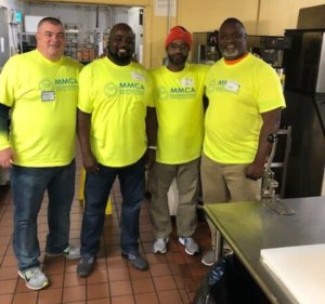 MORCON employees posing in kitchen for a photo, wearing neon yellow shirt and pants